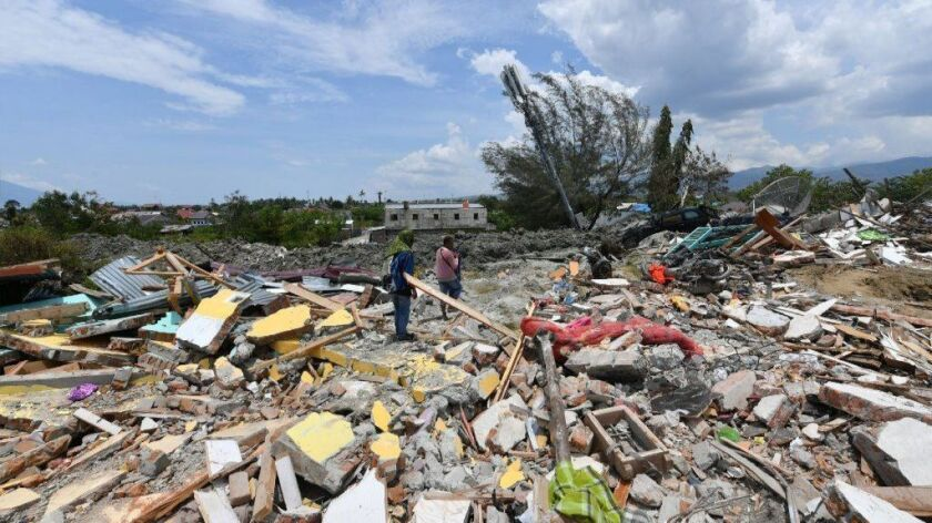 Two men examine debris near where their houses once were in Palu, Indonesia, on Oct. 4, 2018.