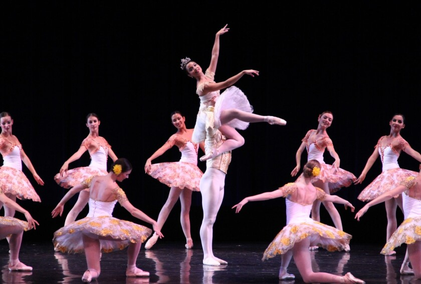 Ballet dancers in tutus stand in a circle during a staging of Paquita