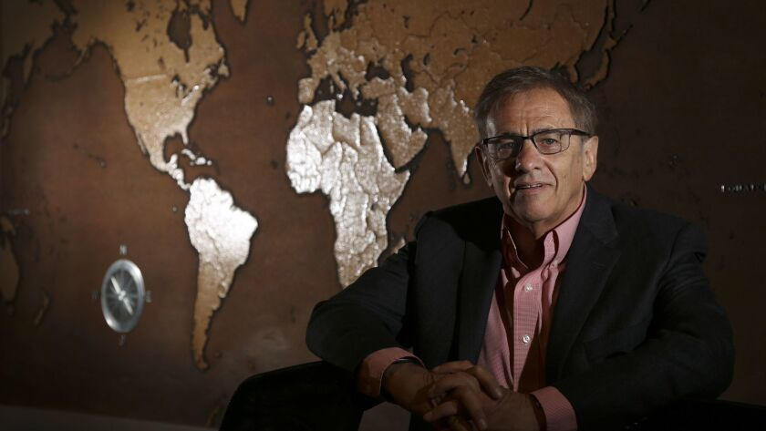 """Rand Corp. President and CEO Michael D. Rich in front of """"Map of the World,"""" a work by former Rand"""