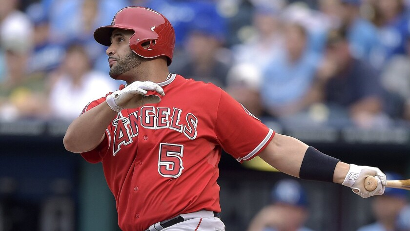 Angels designated hitter Albert Pujols follows through on a run-scoring single during Saturday's game against the Kansas City Royals. Pujols has been playing with a swollen lymph node in his left groin since Wednesday.