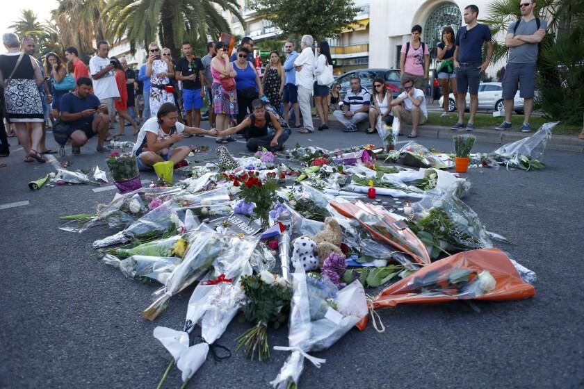 """Varias personas rinden homenaje a las víctimas en el lugar donde un camión arrolló a una multitud en la afamada Promenade des Anglais en Niza, en el sur de Francia, el sábado 16 de julio de 2016. El canciller francés Bernard Cazeneuve dice que el chofer del camión que mató a 84 personas en ese lugar se """"radicalizó con mucha rapidez"""". (AP Foto/Francois Mori)"""