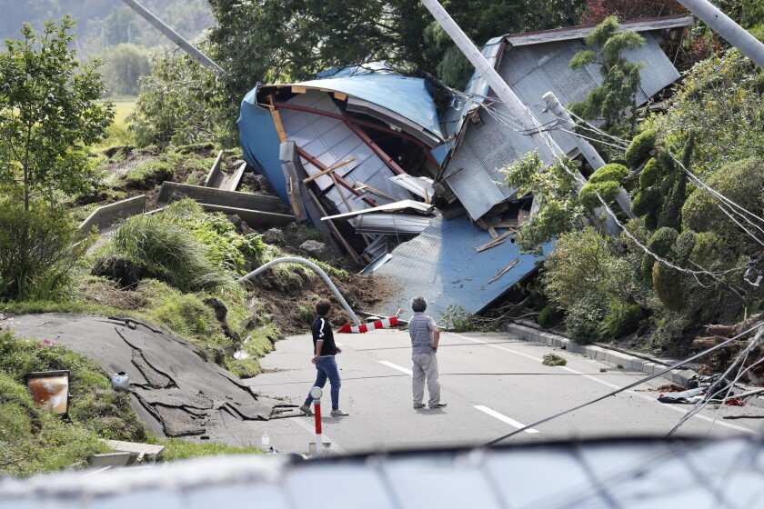 Buildings destroyed by an earthquake-triggered landslide block a road in Atsuma, Japan, on Sept. 6.