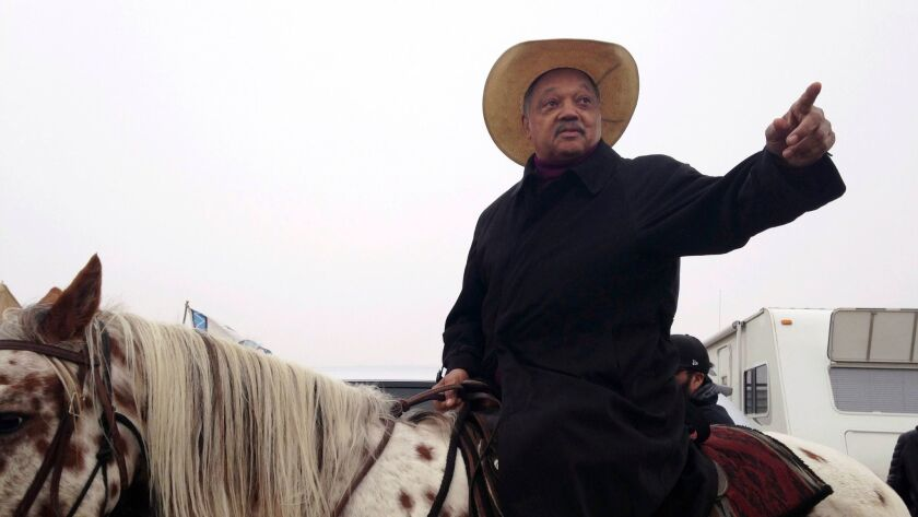 Civil rights activist Jesse Jackson sits atop a horse Wednesday, Oct. 26, 2016, while visiting the protest camp against the Dakota Access oil pipeline outside Cannon Ball, N.D.
