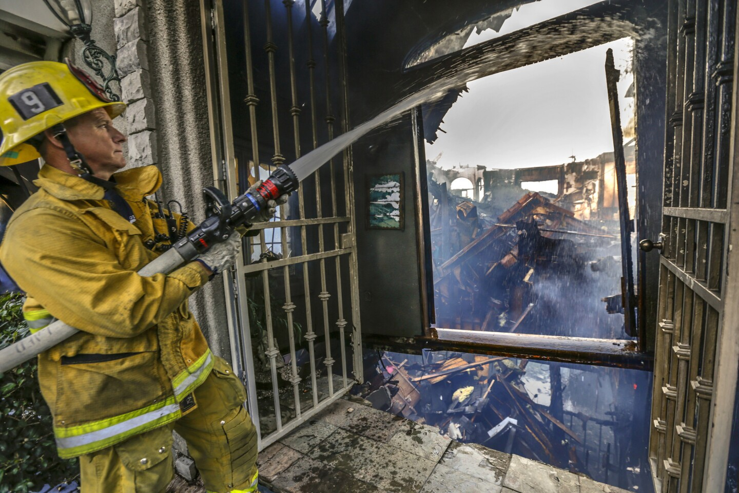 Firefighters continue housing down smoldering ruins after a fire tore through a large hillside home Thursday night in the Mt. Washington neighborhood of Los Angeles.