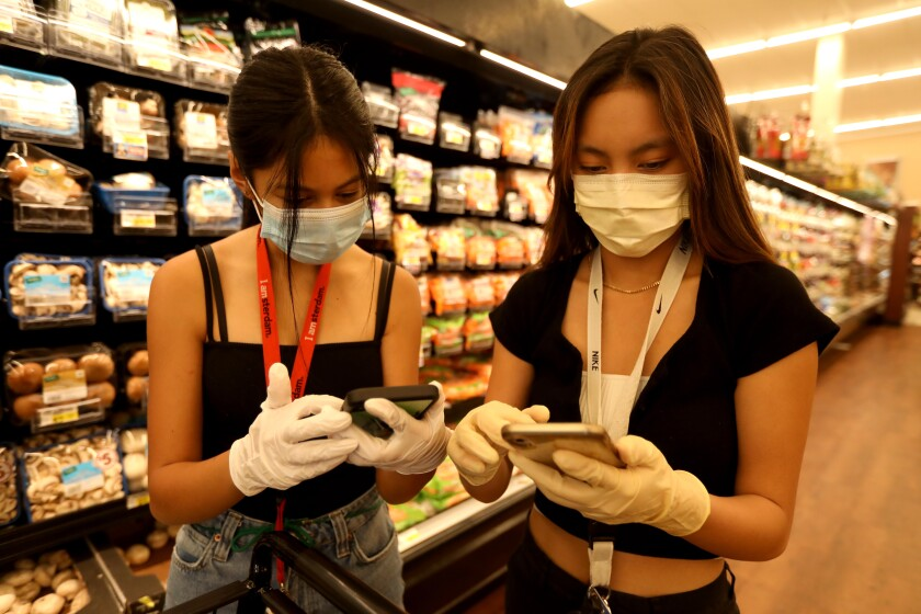 Christine Riel, 16, left, and Krysta Mendoza, 17, juniors at West Ranch High School in Santa Clarita, fill an online order at Albertson's grocery store in Valencia this week. Both are volunteers with Six Feet Supplies, a free service started by local teenagers to help the most vulnerable during the coronavirus outbreak.