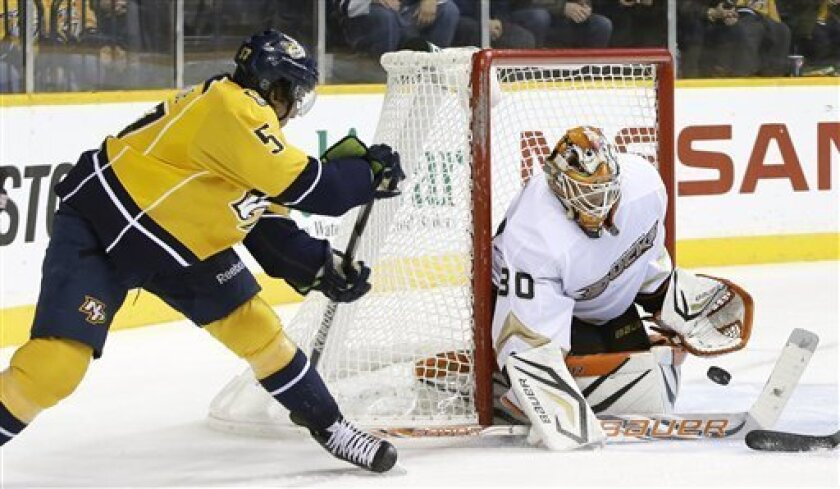 Anaheim Ducks goalie Viktor Fasth (30), of Sweden, blocks a shot as Nashville Predators left wing Gabriel Bourque (57) watches for the rebound in the second period of an NHL hockey game Saturday, Feb. 16, 2013, in Nashville, Tenn. (AP Photo/Mark Humphrey)