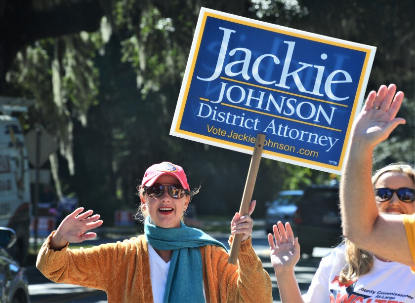 Jackie Johnson, then a district attorney in Georgia, waves and holds a sign for her reelection campaign.