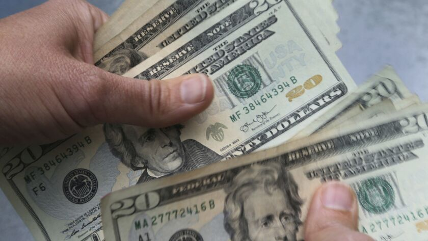 In this June 15, 2018 photo, twenty dollar bills are counted in North Andover, Mass. (AP Photo/Elise