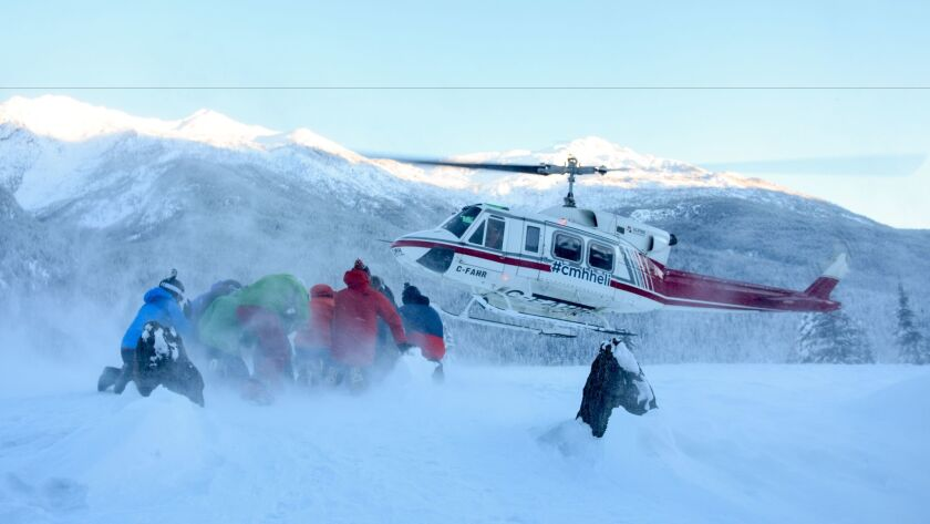 """A group """"€œheli-huddles""""€ as the ski chopper lands at Canadian Mountain Holiday's Cariboos lodge."""
