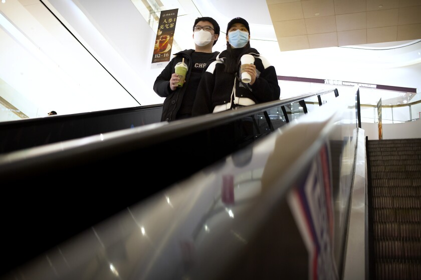 A couple wear face masks as they ride an escalator at a shopping mall in Beijing, Saturday, March 7, 2020. Crossing more borders, the new coronavirus hit a milestone, infecting more than 100,000 people worldwide as it wove itself deeper into the daily lives of millions, infecting the powerful, the unprotected poor and vast masses in between. (AP Photo/Mark Schiefelbein)