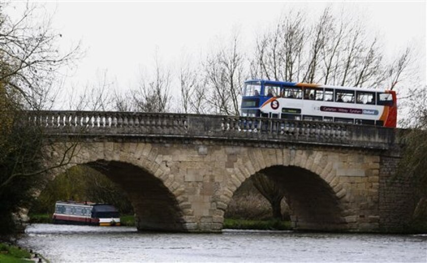 FILE - This is a Wednesday, Nov. 18, 2009 file photo shows a bus being driven over the Swinford Toll Bridge over the River Thames in Oxfordshire, England. The toll bridge built in 1769 has sold for more than 1 million pounds ($1.66 million) at auction. The Swinford bridge brings in about 190,000 pounds (US$320,000) in toll payments from about 4 million vehicle crossings a year. Due to a quirk in British law, toll revenue collected from the picturesque stone structure about 65 miles (100 kilometers) northwest of London can be collected tax-free. (AP Photo/Kirsty Wigglesworth, File)