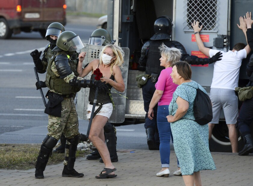 "A woman fights with a police officer as the other police officers detain an opposition supporter protesting the election results as protesters encounter aggressive police tactics in the capital of Minsk, Belarus, Tuesday, Aug. 11, 2020. Heavy police cordons blocking Minsk's central squares and avenues didn't discourage the demonstrators who again took to the streets chanting ""Shame!"" and ""Long live Belarus!"" Police moved quickly Tuesday to separate and disperse scattered groups of protesters in the capital, but new pockets of resistance kept mushrooming across downtown Minsk. (AP Photo)"