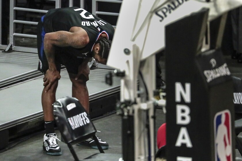 Los Angeles Clippers forward Kawhi Leonard holds his knee after stepping awkwardly during the second half against Utah.