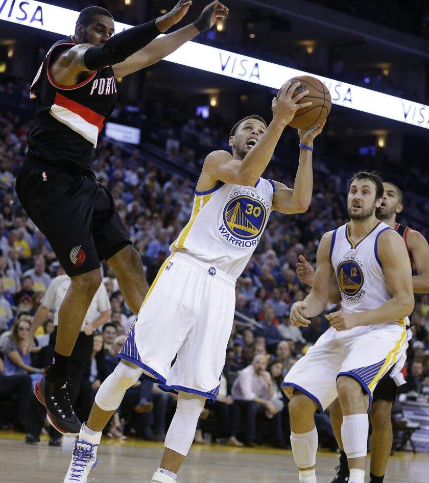 Golden State Warriors' Stephen Curry, center, shoots beneath Portland Trail Blazers' LaMarcus Aldridge, left, during the second half of an NBA basketball game Thursday, April 9, 2015, in Oakland, Calif. The Warriors won 116-105. (AP Photo/Ben Margot)