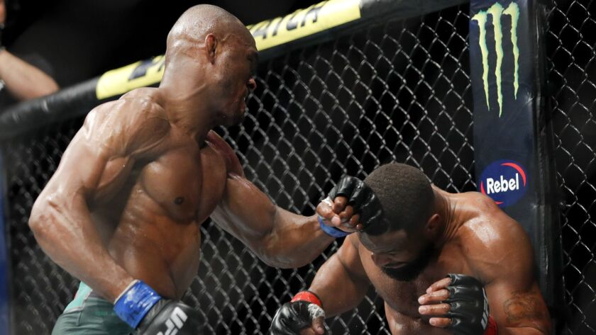 Kamaru Usman, left, hits Tyron Woodley during a welterweight mixed martial arts title fight at UFC 2