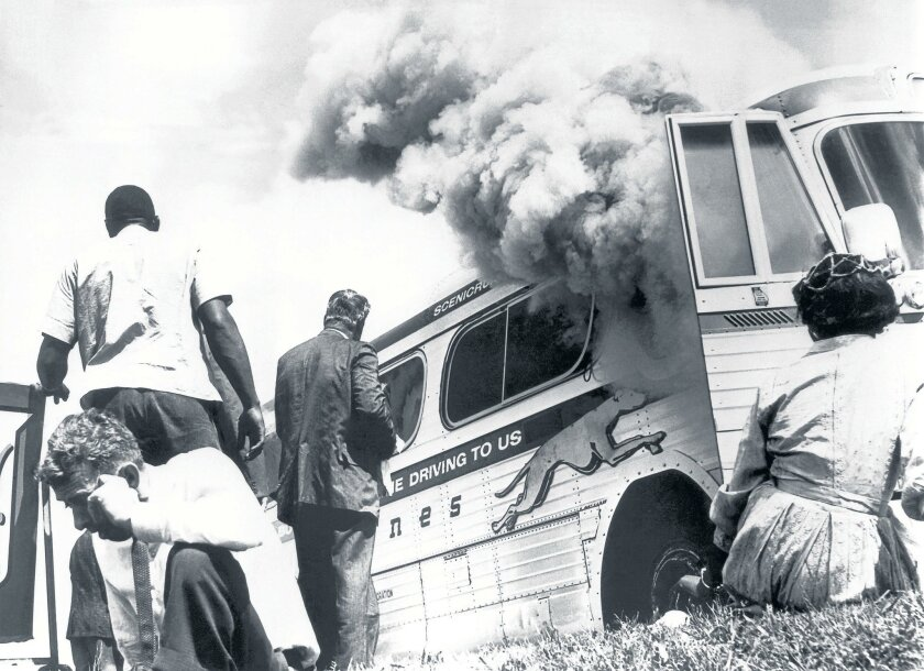 Freedom Riders escape a Greyhound bus after it was set afire in Anniston, Ala., on May 14, 1961.