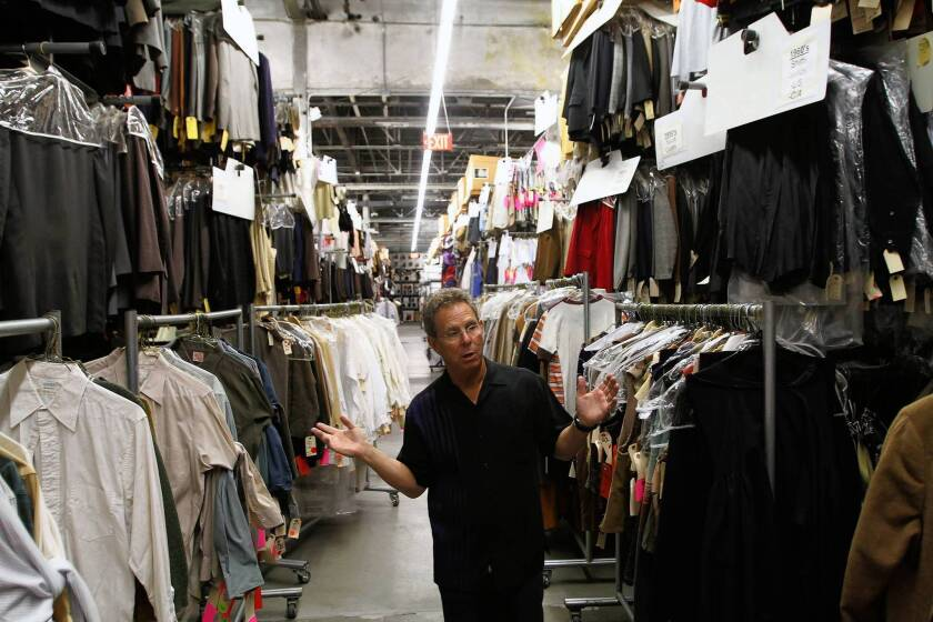 Eddie Marks, president of Western Costume, stands amid rows of garments that are sorted by decade.