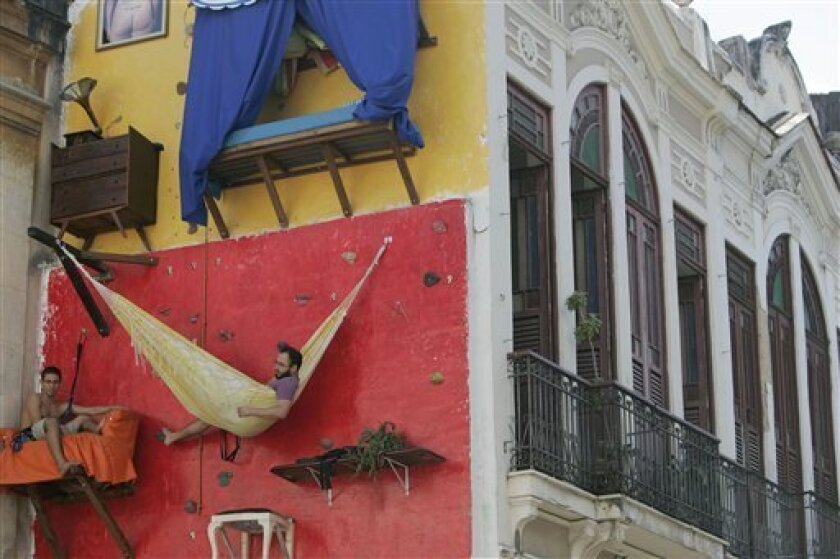 Brazilian artists Gabriel Primo, left, and Tiago Primo sit in their installation art work, exhibited on the wall of a building, in Rio de Janeiro, Thursday, July 9, 2009. (AP Photo/Ricardo Moraes)