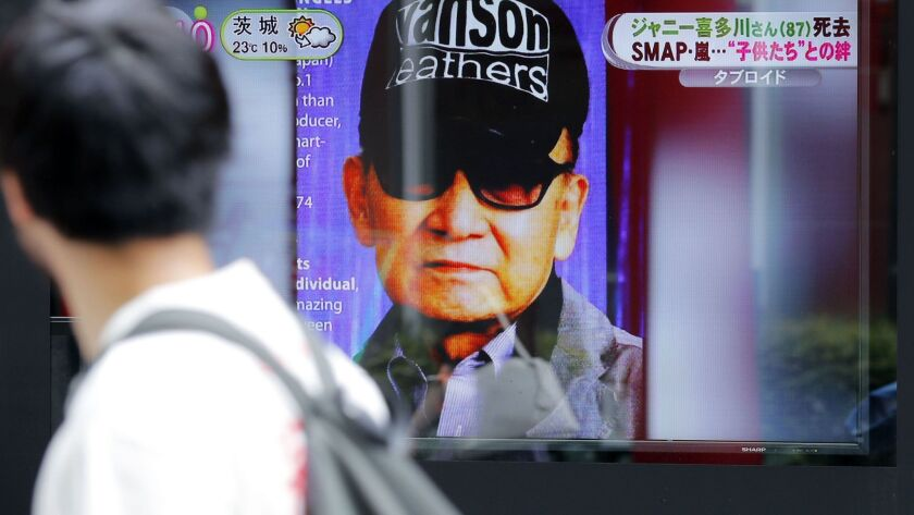 A passer-by watches a TV news reporting Johnny Kitagawa's passing away in Tokyo Wednesday, July 10,