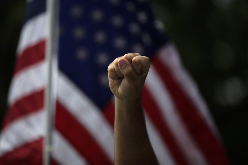 FILE - In this June 1, 2020, file photo a demonstrator raises his fist during a protest over the death of George Floyd, in Anaheim, Calif. The three month stretch between the symbolic kickoff and close of America's summer has both galvanized broad public support for the racial justice movement and exposed the obstacles to turning that support into concrete political and policy changes. (AP Photo/Jae C. Hong, File)