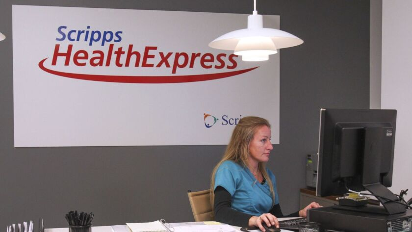 Medical Assistant Janine Pitzer works at the front desk at the UTC Scripps HealthExpress clinic in 2015. Scripps plans to add a dozen more of the small facilities at existing medical office complexes by the end of September.