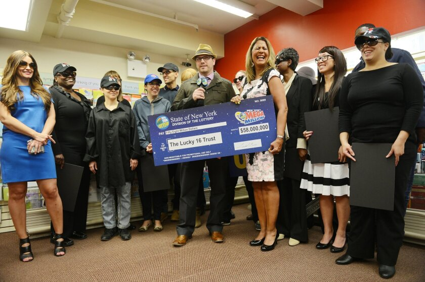 One of the winners Kevin Berth, center left, stands with Yolanda Vega as she presents an oversized check to a group of colleagues that call themselves the Lucky 16 Trust, at Carlton Cards inside Penn Station where a media conference was held for the $58 million Mega Millions jackpot winners Thursda