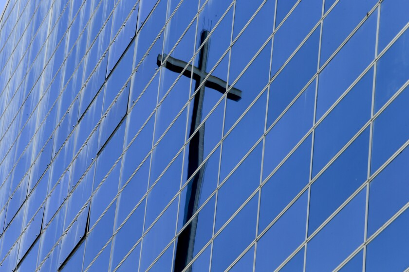 A cross is reflected on a building