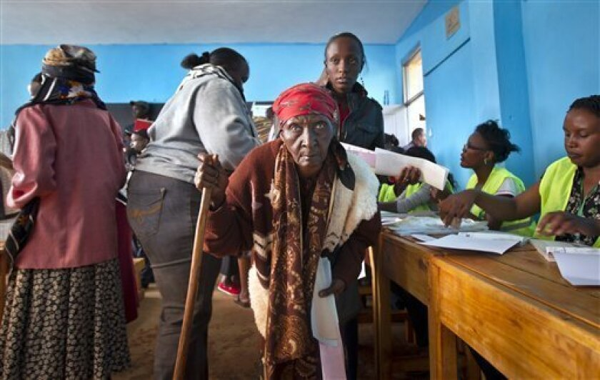 An elderly lady walks with a cane to cast her vote in the Mutumo primary school near Gatundu, north of Nairobi, in Kenya Monday, March 4, 2013. Multiple attacks against security forces in Kenya on Monday killed at least 12 people as Kenyans waited in long lines to cast ballots five years after more than 1,000 people died in election-related violence. (AP Photo/Ben Curtis)