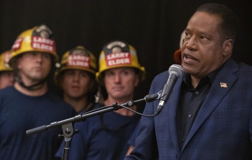 "Larry Elder speaks into a microphone next to firefighters with ""Larry Elder"" helmets"