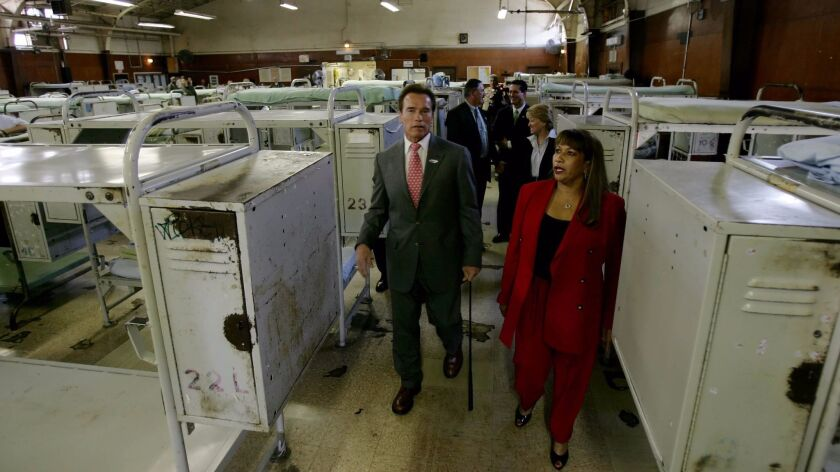 Then-Gov. Arnold Schwarzenegger, left and California Rehabilitation Center Warden Guillermina Hall, right, tour a prison gym in March 2007 in Norco, Calif.
