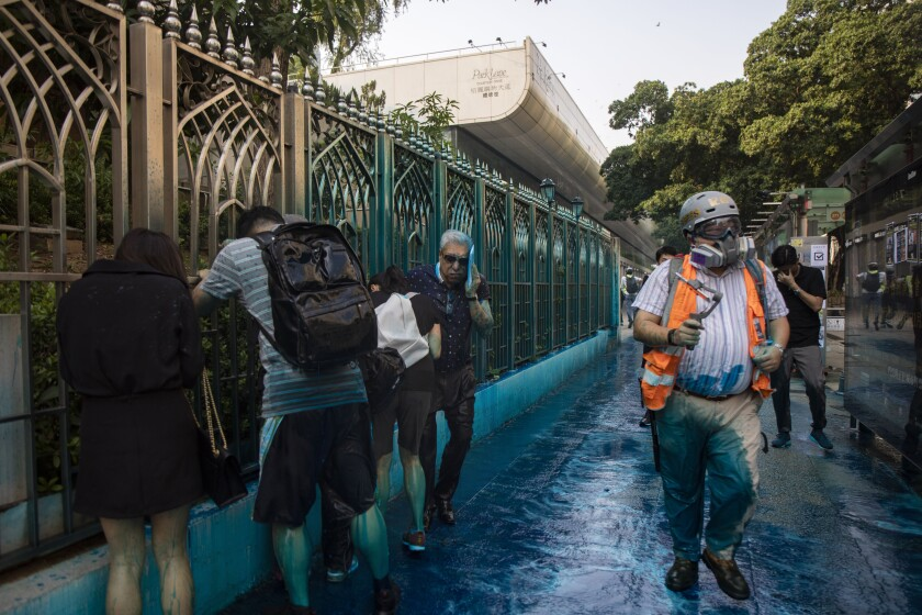 People react after sprayed with blue-dyed water by a police riot-control vehicle during a protest outside the Kowloon Mosque in Hong Kong. Hong Kong officials apologized to leaders of the Kowloon Mosque afterward.