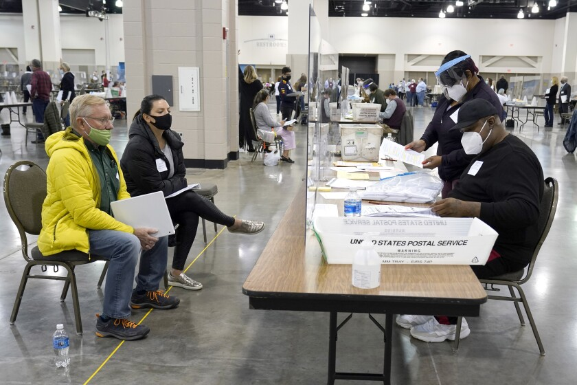 Election workers verify ballots during a Milwaukee hand recount of presidential votes at the Wisconsin Center