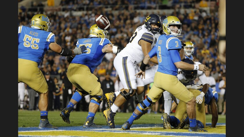 UCLA quarterback Josh Rosen fumbles the ball in the end zone under pressure by California defensive lineman Luc Bequette (93) and linebacker Raymond Davison III (31) during the first half.