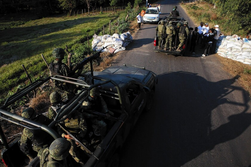 Mexican soldiers inspect a checkpoint manned by members of a self-defense militia, who block a road to impede the possible access of the Knights Templar drug cartel, in Mexico's Michoacan state.