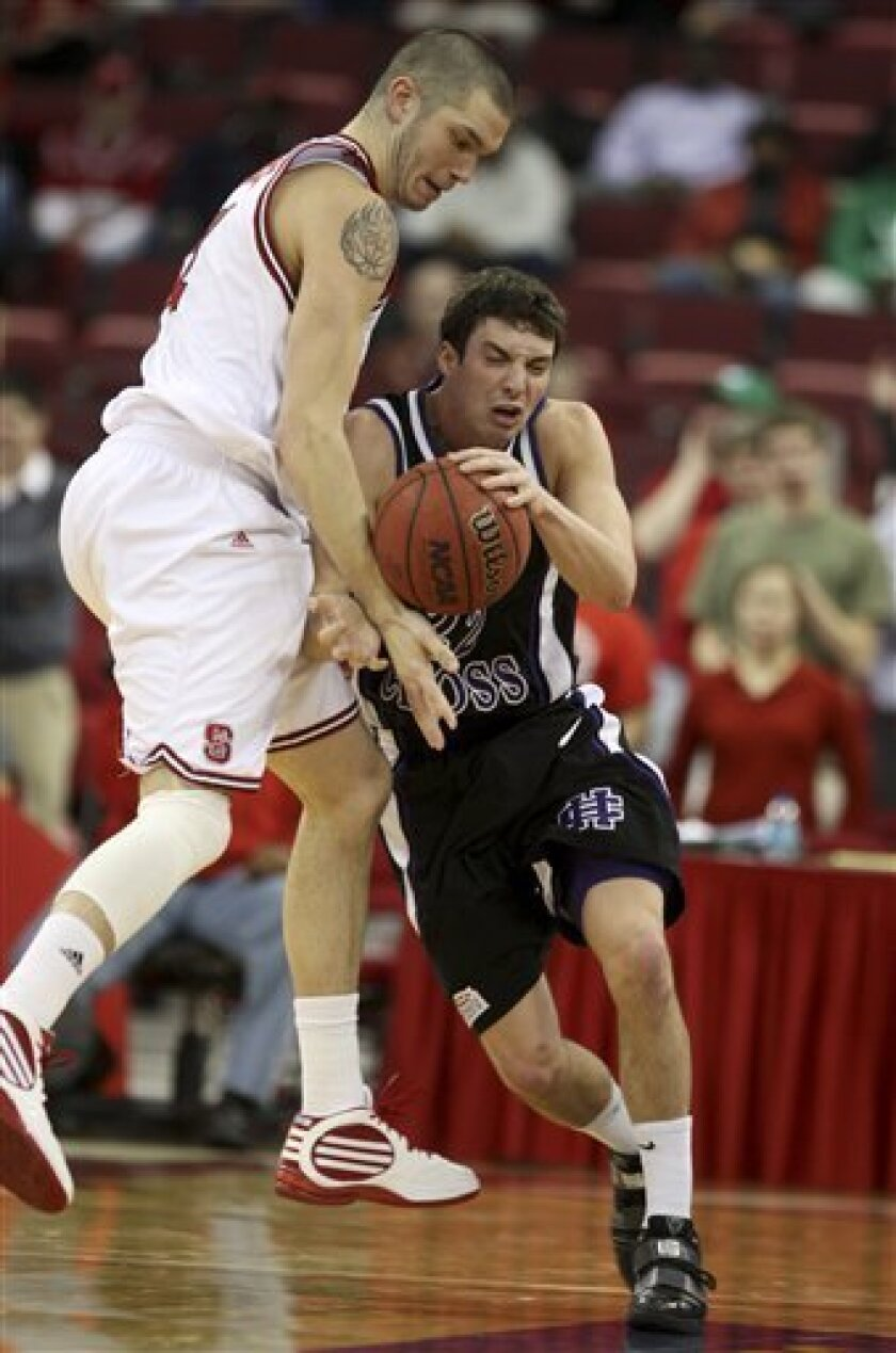 Holy Cross' Andrew Beinert (22) runs into North Carolina State's Dennis Horner (31), losing the ball during the first half of an NCAA college basketball game Wednesday, Jan. 6, 2010, in Raleigh, N.C. (AP Photo/The News & Observer, Ethan Hyman)