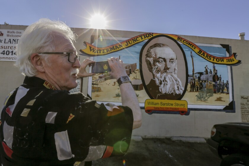 "Canadian tourist Wayne Webb stops to take a photo of the mural ""Waterman Junction Becomes Barstow, 1886,"" on a building along Main Street in Barstow."