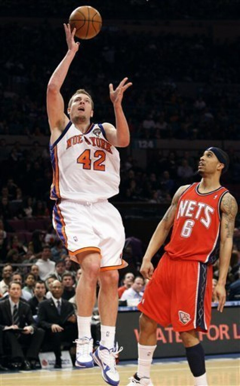 New York Knicks' David Lee (42) drives past New Jersey Nets' Courtney Lee (6) during the first half of an NBA basketball game Saturday, March 6, 2010, in New York. (AP Photo/Frank Franklin II)