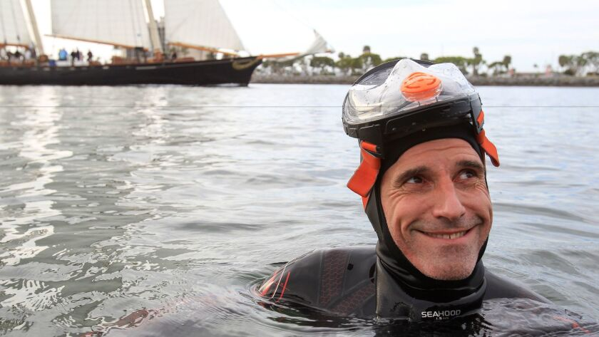 As a sail boat passes behind him, long distance swimmer Ben Lecomte, 49, looks up at his crew on the