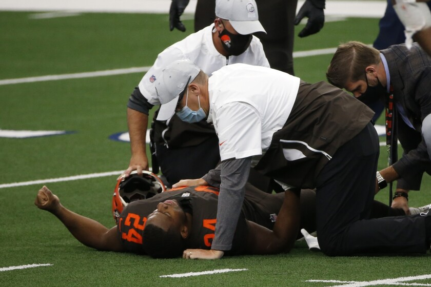 Cleveland Browns running back Nick Chubb (24) receives assistance from team staff after suffering an unknown injury in the first half of an NFL football game against the Dallas Cowboys in Arlington, Texas, Sunday, Oct. 4, 2020. (AP Photo/Michael Ainsworth)