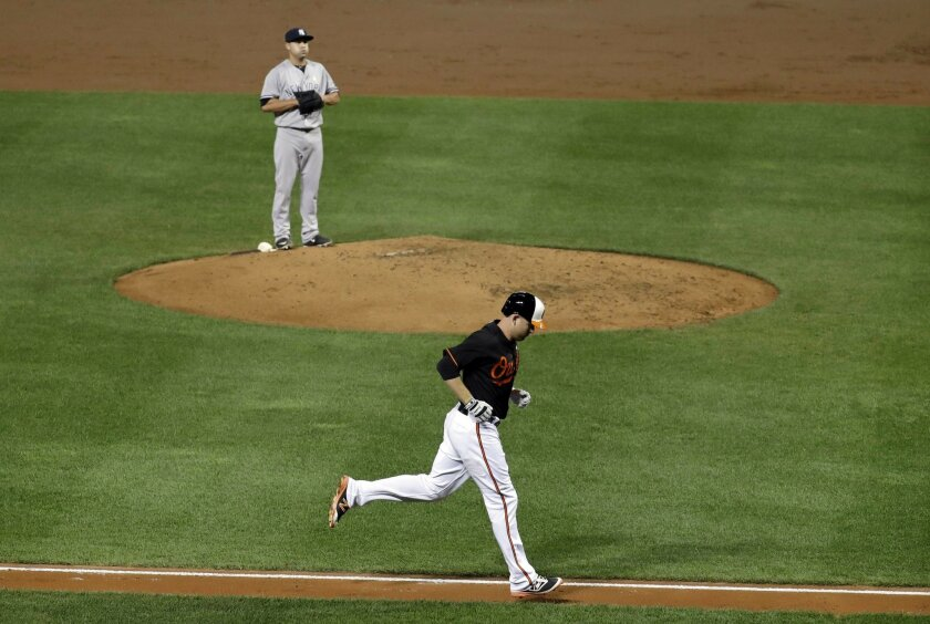 Baltimore Orioles' Mark Trumbo, bottom, rounds the bases on a solo home run past New York Yankees relief pitcher Nick Goody in the second inning of a baseball game in Baltimore, Friday, Sept. 2, 2016. (AP Photo/Patrick Semansky)