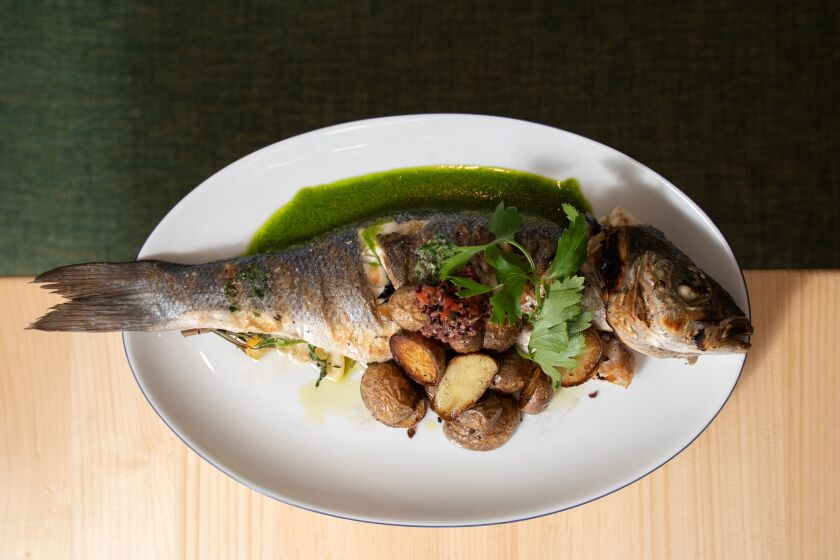 The whole loup de mer, aka seabass, at Candor in La Jolla, is serves with lemon herb stuffing, marble potatoes, red pepper tapenade and salsa verde.