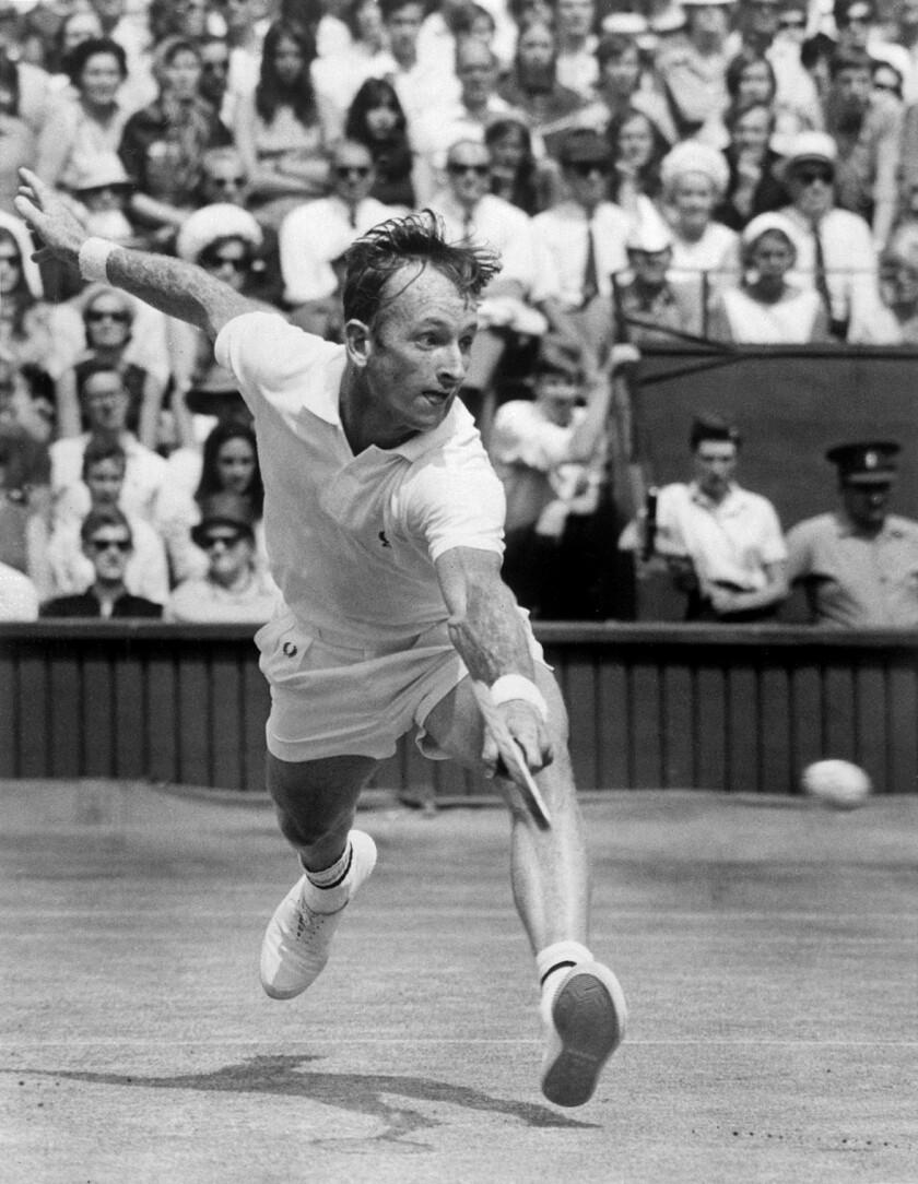 Rod Laver, shown beating Tony Roche during the 1968 Wimbledon men's singles championship, won a calendar-year grand slam in 1969.
