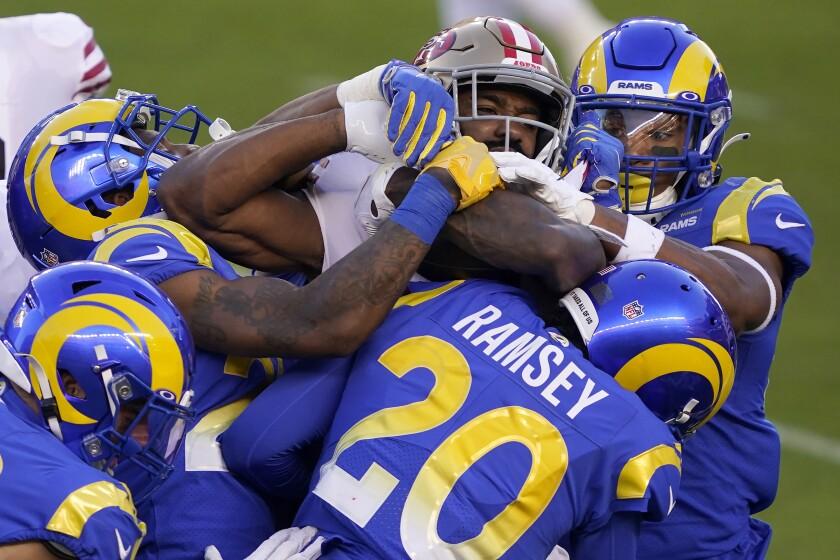 San Francisco 49ers running back Raheem Mostert, center, is tackled by Los Angeles Rams defenders during the first half of an NFL football game in Santa Clara, Calif., Sunday, Oct. 18, 2020. (AP Photo/Tony Avelar)
