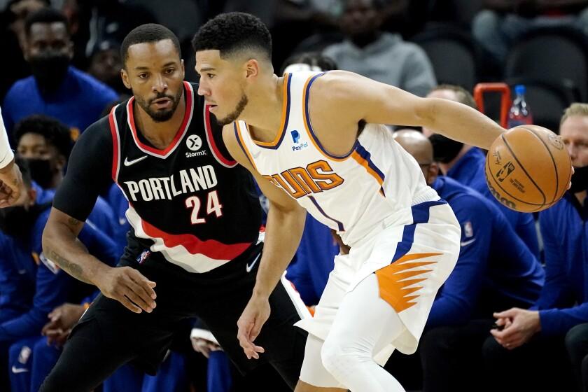 Phoenix Suns guard Devin Booker (1) looks to pass as Portland Portland Trail Blazers forward Norman Powell (24) defends during the first half of a preseason NBA basketball game, Wednesday, Oct. 13, 2021, in Phoenix. (AP Photo/Matt York)