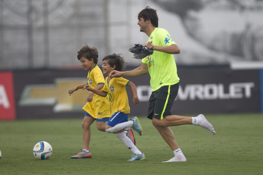 El jugador de la selección Brasil Kaká juega con su hijo Luca (c) y otro niño amigo durante una sesión de entrenamiento hoy, martes 10 de noviembre de 2015, en el club Corinthians de la ciudad de Sao Paulo (Brasil). Brasil enfrentará a Argentina el próximo jueves 12 de noviembre en partido por las eliminatorias sudamericanas del Mundial de Rusia 2018.