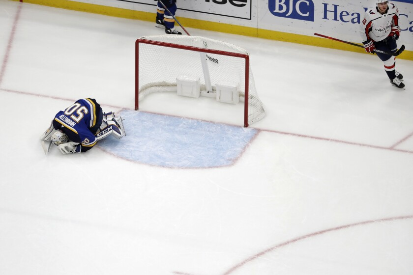 St. Louis Blues goaltender Jordan Binnington, left, reacts after giving up the game-winning goal to Washington Capitals' Jakub Vrana, right, of the Czech Republic, during overtime of an NHL hockey game, Wednesday, Oct. 2, 2019, in St. Louis. The Capitals won 3-2 in overtime. (AP Photo/Jeff Roberson)