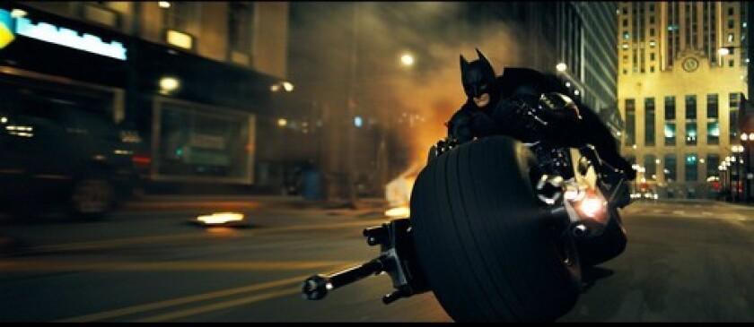 "Christian Bale patrols the streets of Gotham as Batman in ""The Dark Knight."""
