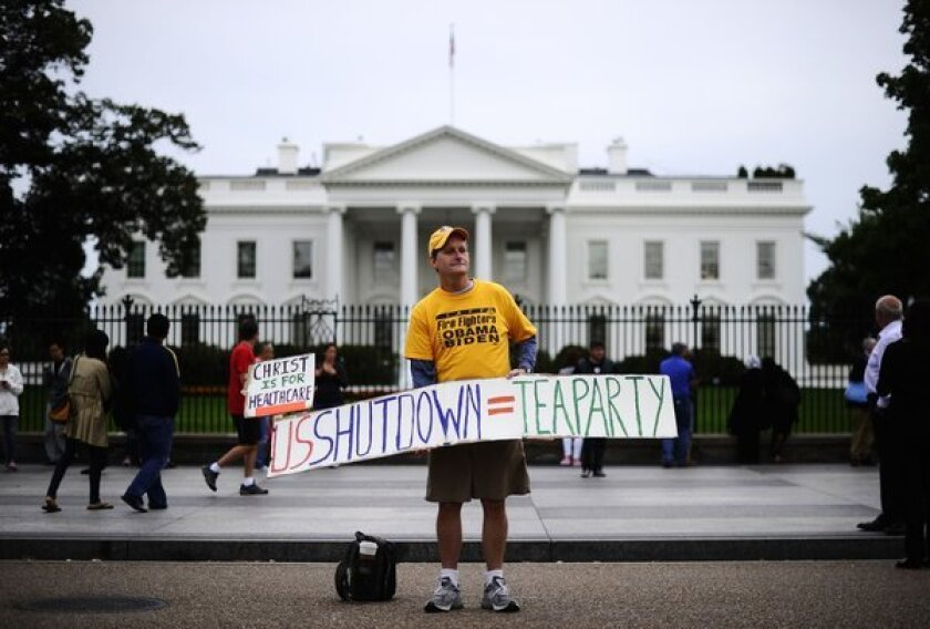A supporter of President Obama holds a placard blaming the tea party for the government shutdown Tuesday in front of the White House.
