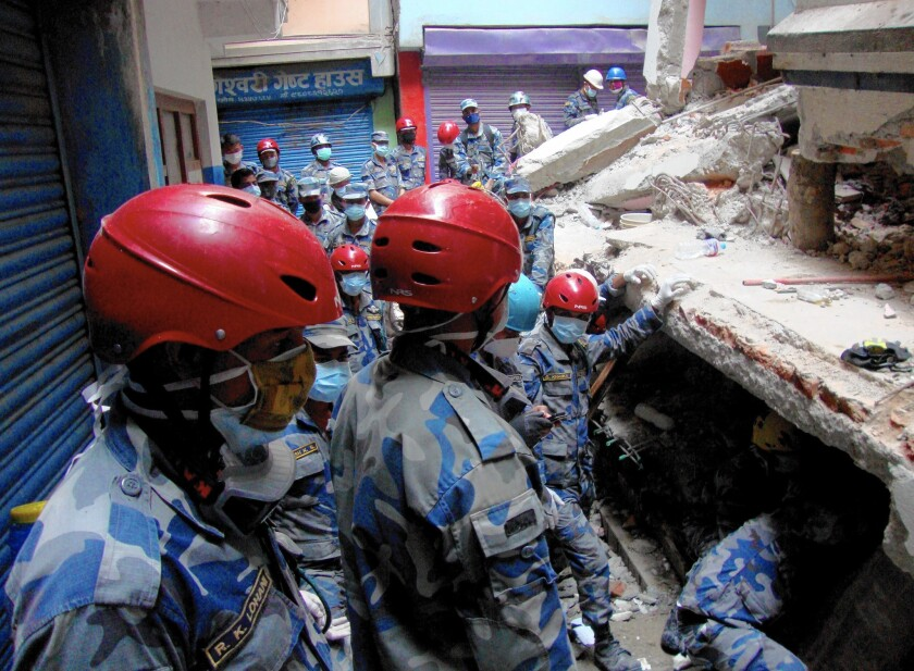 A rescue team searches under a collapsed building in the Gongabu neighborhood of Katmandu, Nepal, for a body in the aftermath of the earthquake.