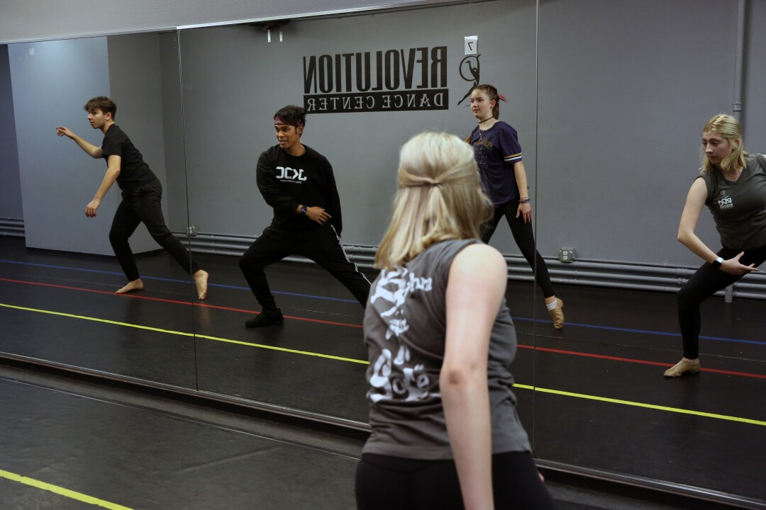 Fred Diaz, second from left, and three dance students reflected in a mirror and a view from behind of one of the students, a blond woman.